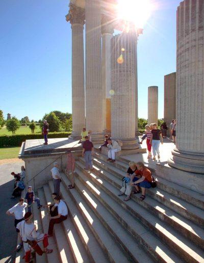 Das Foto zeigt einen Ausschnitt der Teilrekonstruktion des römischen Hafentempels im LVR-Archäologischen Park. Menschen halten sich bei Sonnenlicht auf der Treppe und zwischen den Säulen auf.