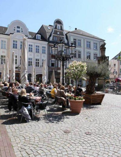 Das Foto zeigt den Altmarkt im Herzen der Moerser Innenstadt. Die verschiedenen Gastronomieangebote rund um den Platz laden zum Verweilen in der Altstadt ein.