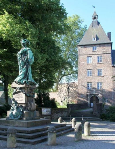 Das Foto zeigt das Moerser Schloss mit dem Grafschafter Museum. Vor dem Schloss steht die Statue von Luise Henriette von Oranien.