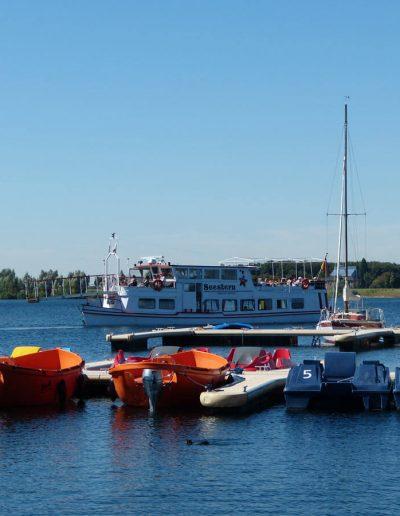 Das Foto zeigt Elektro- und Tretboote, die im Hafen liegen. Im Hintergrund befindet sich das Fahrgastschiff Seestern, das auf der Nord- und Südsee seine Runden dreht.