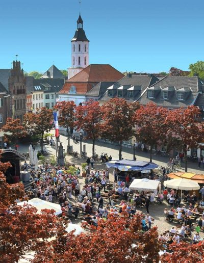 Das Foto zeigt den belebten Marktplatz bei schönem Wetter. Die Menschen feiern ein Fest. Im Hintergrund erhebt sich hinter einer Baumreihe die kleine evangelische Barockkirche.